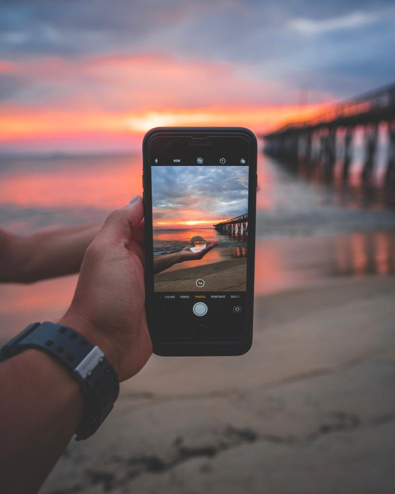 person_holding_black_smartphone_near_seashore_and_dock_under_cloudy_sky_during_golden_hour-scopio